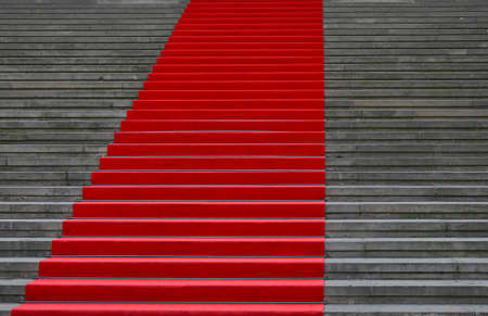 Close up red carpet over grey concrete stairs perspective ascending, low angle view 写真素材