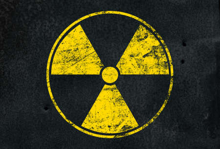 Yellow radioactive hazard warning sign painted over grunge black metal wall background with copy space Imagens - 120444931