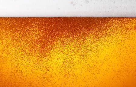 Nahaufnahme der Hintergrundtextur von Lagerbier mit Blasen und Schaum im Glas, Seitenansicht mit niedrigem Winkel