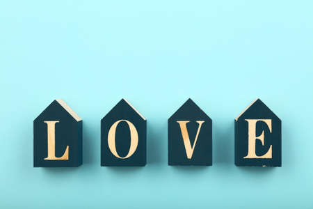 Wooden house shaped cube signs with LOVE word over pastel blue background and copy space, low angle view