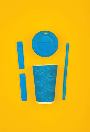 Close up one crimped disposable blue paper takeaway cup, plastic cap, two sugar sachets and drinking straw over vivid yellow background, flat lay, elevated top view, directly above Stock fotó