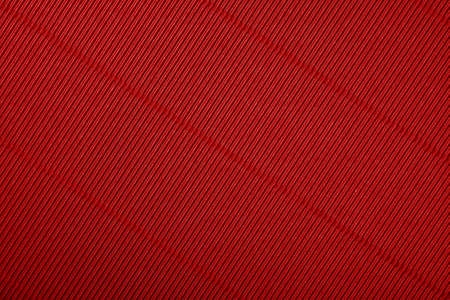 Close up diagonal background pattern texture of vivid scarlet red corrugated packaging cardboard