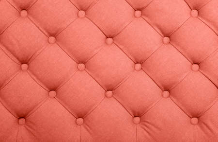 Coral toned pink capitone textile background, retro Chesterfield style checkered soft tufted fabric furniture decoration with buttons, close up