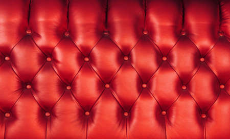 Background texture of scarlet red capitone genuine leather, retro Chesterfield style soft tufted furniture upholstery with deep diamond pattern and buttons, close up 写真素材