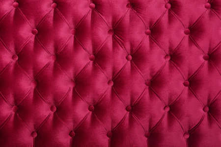 Burgundy dark red velvet capitone textile background, retro Chesterfield style checkered soft tufted fabric furniture diamond pattern decoration with buttons, close up Banco de Imagens