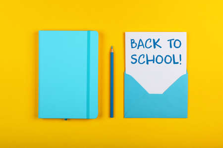 Back to school handwritten sign on white paper in blue envelope next to leather cover notebook over yellow paper background