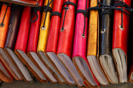 Close up many handmade colorful leather cover notebooks on retail display, high angle view Stock fotó