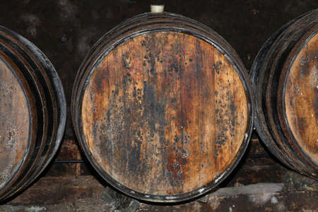 Close up rows of traditional aged natural oak wood wine barrels in winery cellar Фото со стока
