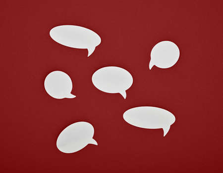 Group of six different shape blank empty white paper speech bubble callouts over red background 写真素材