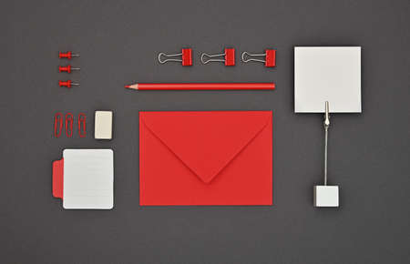Neatly organized red stationery flat lay of notes, envelope, pencil, office clips, binders and pins in order over dark grey background, elevated top view, directly above Stock Photo