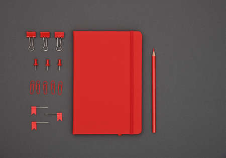 Neatly organized red stationery flat lay of notebook, pencil, office clips, binders and pins in order over dark grey background, elevated top view, directly above
