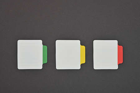 Close up three blank white paper notes with colorful labels over grey background Reklamní fotografie