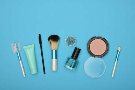 Feminine beauty care flat lay of face makeup blush, brushes, nail polish and glitter over blue background, elevated top view, directly above 写真素材 - 129799300