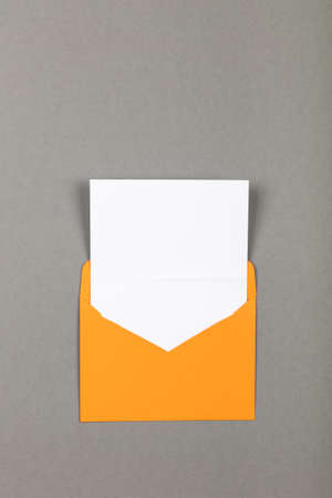 One open blank vivid yellow envelope with white paper over grey background, flat lay, directly above