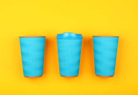 Close up three crimped disposable pastel blue paper takeaway coffee cups with plastic cap over vivid yellow background, flat lay, elevated top view, directly above
