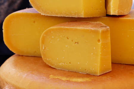 Close up cut slices and wheel of hard matured yellow gouda Dutch cheese, low angle view Stock fotó