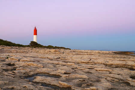 Rocky sea coast landscape with lighthouse over clear pink sunset sky, low angle view