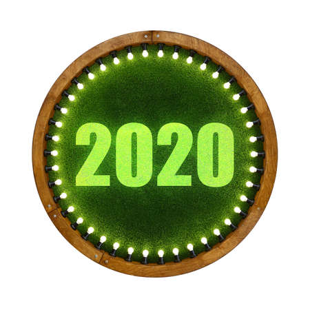 Close up 2020 sign over round shape wooden ring light frame with lightbulbs and backdrop of illuminated vivid green plastic artificial grass, isolated on white background