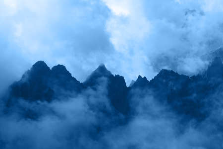 Blue toned landscape of dark rocky mountain ridge silhouette in foggy clouds, High Tatra mountains