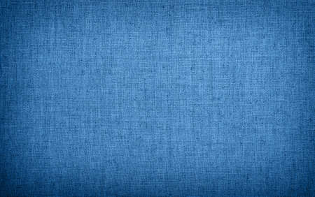 Natural rustic blue toned classic flax linen fabric textile sackcloth bagging canvas texture pattern background with darker border shade vignette