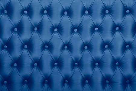 Dark blue capitone textile background, classic retro Chesterfield style checkered soft tufted fabric furniture diamond pattern decoration with buttons, close up Imagens