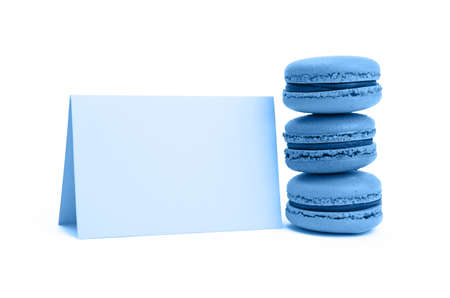 Close up stack of traditional French blue macaroon pastry cookies (macarons, macaroni) with paper sign isolated on white background, low angle view