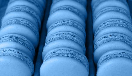 Close up fresh baked blue macaroon pastry cookies (macarons, macaroni) in retail store display, high angle view Imagens