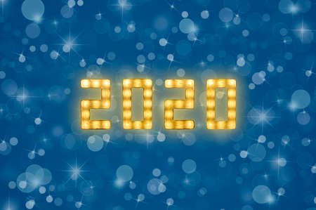 Close up yellow neon glowing bright led light 2020 sign on winter snowflakes and bokeh blue background with copy space