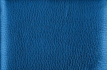 Close up background texture pattern of dark blue natural classic leather grain, directly above