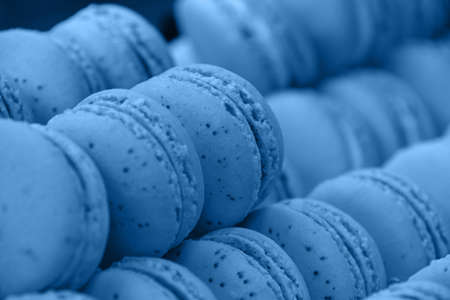 Close up fresh baked blue macaroon pastry cookies (macarons, macaroni) in retail store display, low angle view