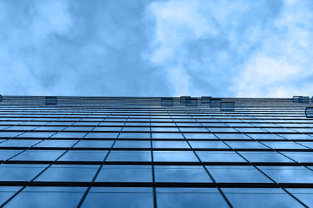 Background texture of modern business skyscraper building glass windows pattern with reflection over cloudy blue sky, low angle view Imagens