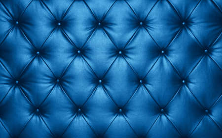 Close up background texture of dark blue capitone genuine leather, classic retro Chesterfield style soft tufted furniture upholstery with deep diamond pattern and buttons