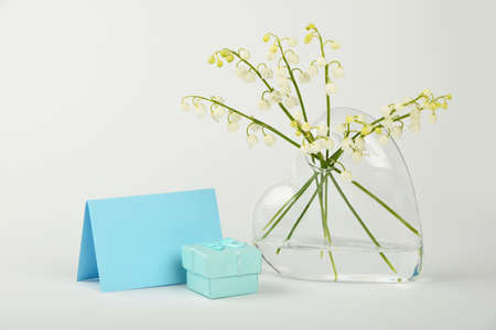 Close up bouquet of lily of the valley fresh spring flowers in heart shaped transparent glass vase over white background with copy space, low angle view