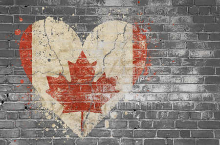 Grunge distressed heqart shaped flag of Canada painted on old weathered grey brick wall