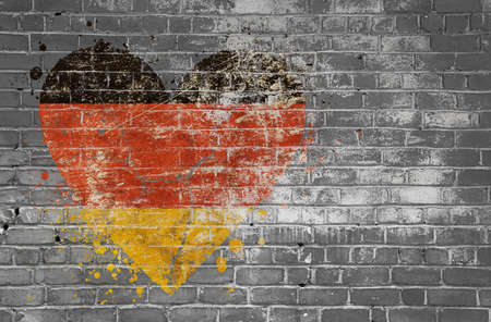 Grunge distressed heqart shaped flag of Germany painted on old weathered grey brick wall Stok Fotoğraf