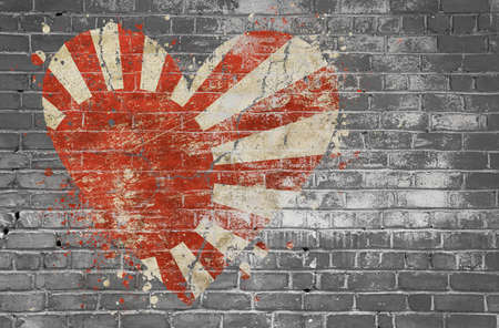 Grunge distressed heqart shaped flag of Japan painted on old weathered grey brick wall