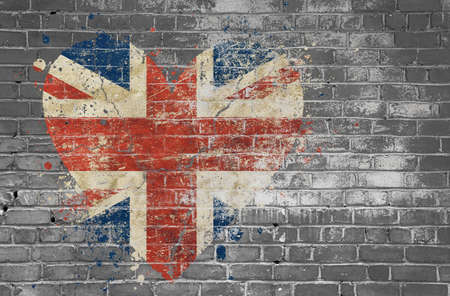 Grunge distressed heqart shaped flag of Britain painted on old weathered grey brick wall