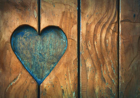 One heart shape, symbol of love and romance, wood carved cut in vintage old grunge natural brown wooden planks of window shutters