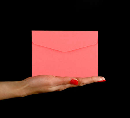 Woman hand palm with red nails holding and presenting pink paper envelope over black background, side view Stok Fotoğraf
