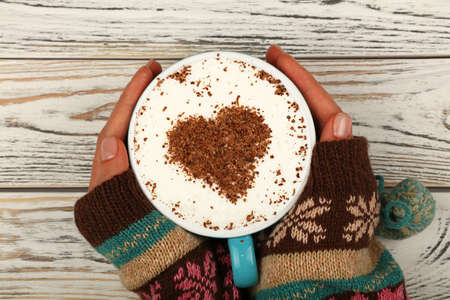 Close up two woman hands hold and hug big full cup of latte cappuccino coffee with heart shaped chocolate on milk froth over white wooden table, elevated top view, directly above Stok Fotoğraf