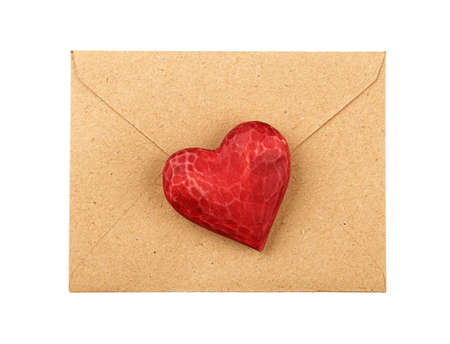 Close up one red painted natural wooden carved heart over brown paper envelope isolated on white background