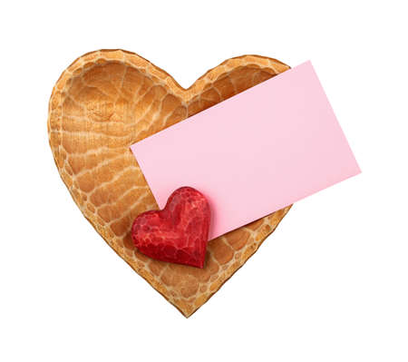 Close up one red painted natural wooden carved heart over pink paper envelope in heart shaped bowl isolated on white background