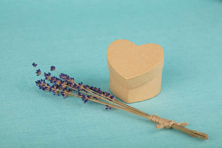 Close up bouquet of dried lavender flowers and small heart shaped gift box on blue tablecloth, high angle view