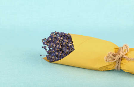 Close up bouquet of dried lavender flowers wrapped in yellow paper on blue tablecloth, high angle view Stok Fotoğraf
