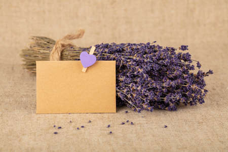 Close up bouquet of dried lavender flowers and small blank paper note message on brown canvas tablecloth, high angle view