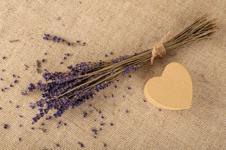 Close up bouquet of dried lavender flowers and small heart shaped gift box on brown canvas tablecloth, elevated top view, directly above Stok Fotoğraf