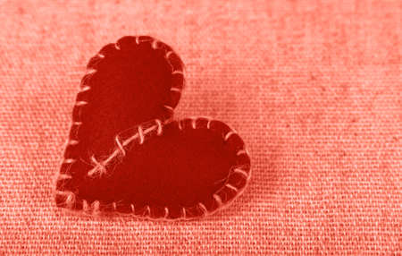 Close up coral pink color toned Valentine Day template, one handmade felt craft stitched toy heart on linen canvas, close up, high angle view