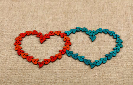 Two hearts together shaped of red and blue handmade wooden sewing buttons on linen canvas, high angle view Stok Fotoğraf