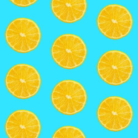 Seamless pattern of fresh ripe orange round cut wedges on pastel blue background