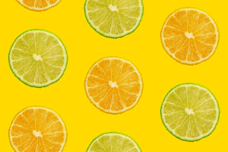 Seamless pattern of fresh ripe orange and lime round cut wedges on yellow teal background Stok Fotoğraf